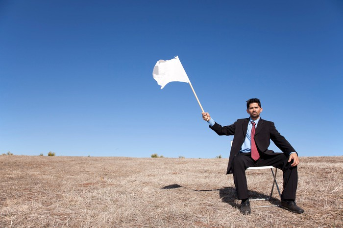 businessman asking for surrendering with a white flag