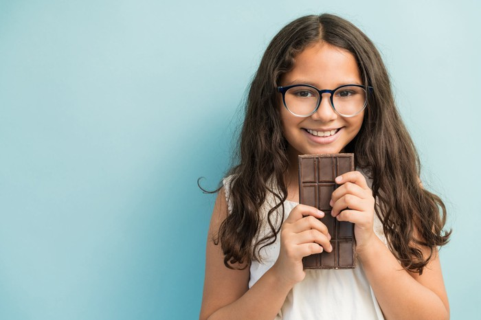 A young girl smiles as she holds a large chocolate bar.