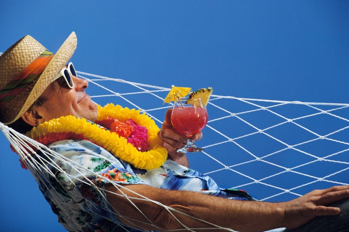 A man lying in a hammock wearing a Panama hat and a lei and holding a drink