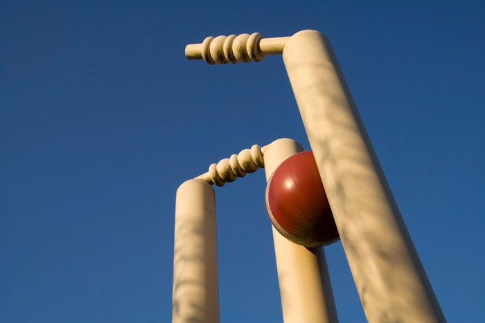 Close-up photo of a cricket ball hitting the wicket.