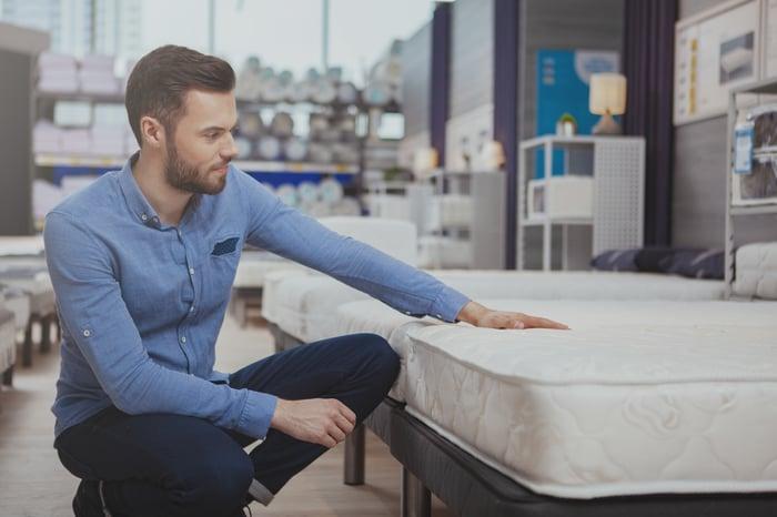 A man inspects a sleep mattress in a store.