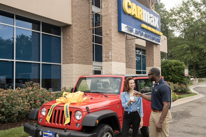A salesperson handing the keys to a customer's new car in the parking lot of a CarMax store.