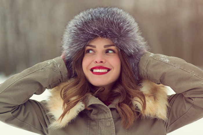 A young woman wearing a coat and fur hat.