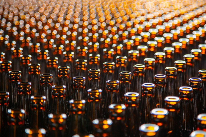 Several rows of brown beer bottles.