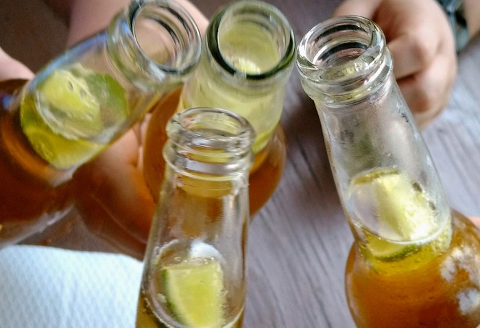 Beer bottles with limes stuck in them