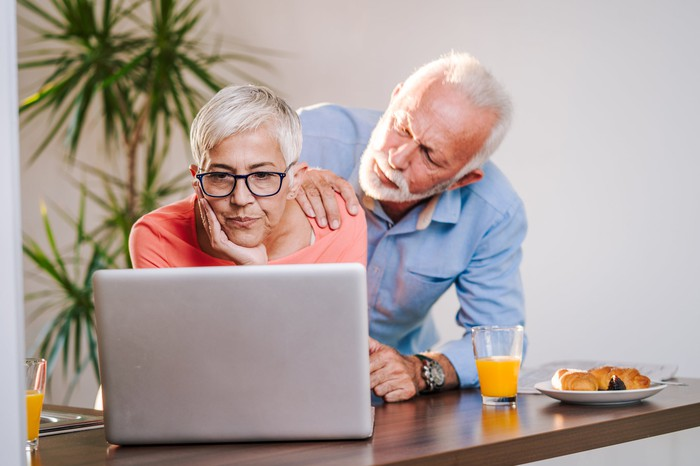 Older woman looking at laptop with serious expression while older man standing behind her touches her shoulder