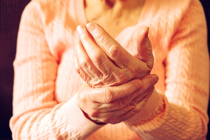 Elderly woman rubbing arthritic hand.