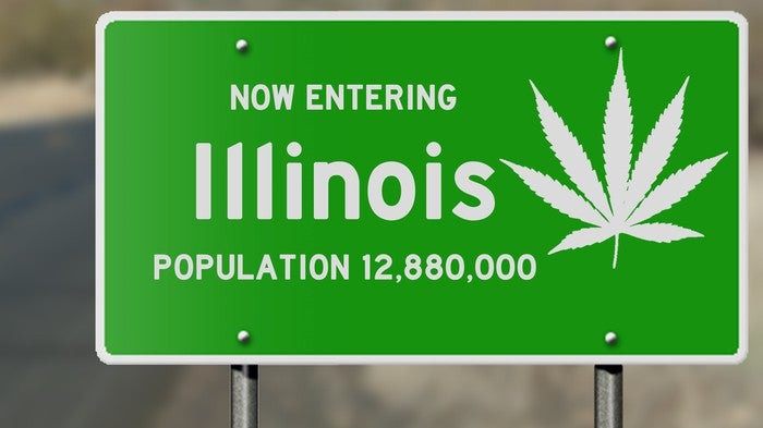 A green highway sign that reads, Now Entering Illinois, with a white cannabis leaf on the right-hand side.