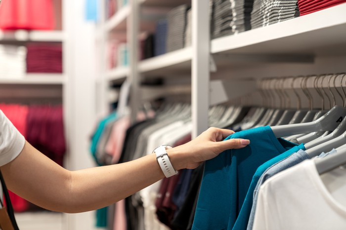 Photograph of woman selecting a shirt in a clothing store.