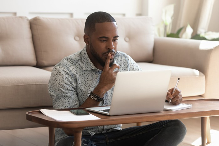 Young black man reviewing information on his laptop