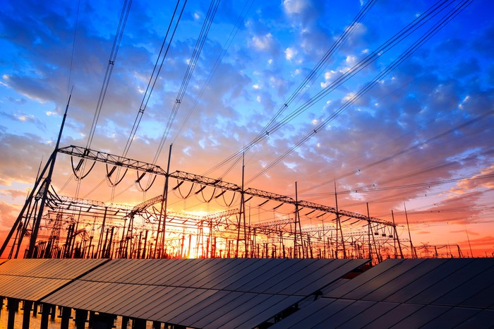 Solar panels and distribution wires stand against the backdrop of a sunset.