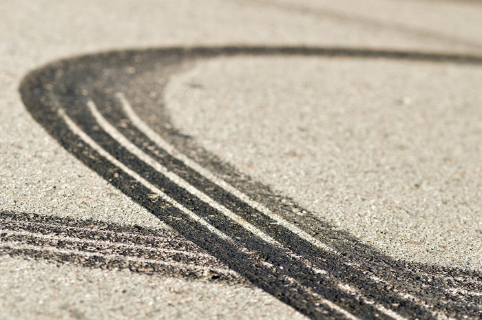 Two car tire skid marks on a road.