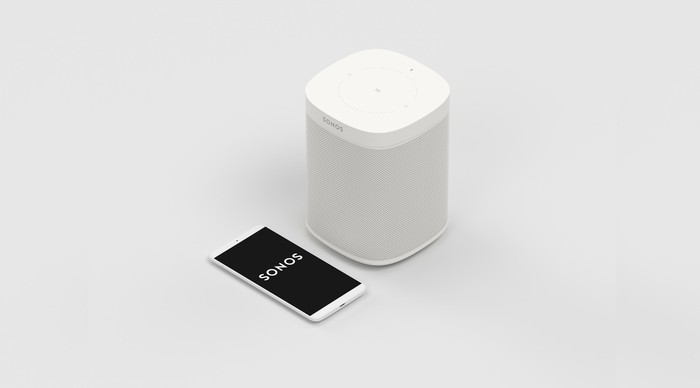 A white Sonos wireless speaker next to a smartphone firing up the Sonos app.