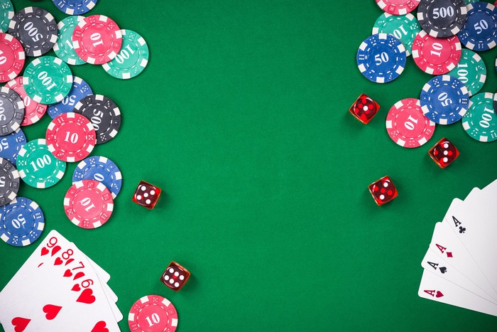 Casino table with red dice; red, blue, green, and black poker chips; a set of cards showing a straight flush, and another showing four aces.