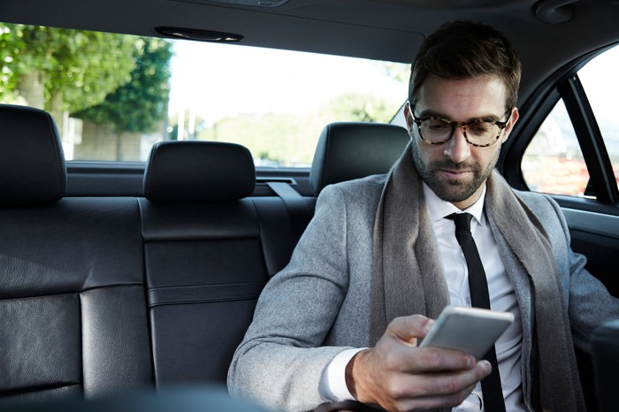 A businessman looking at his smartphone while in the back of a taxi cab.