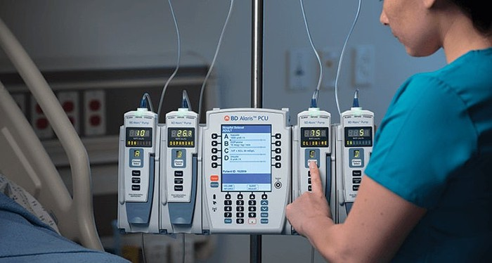 Technician pushing a button on an Alaris infusion system