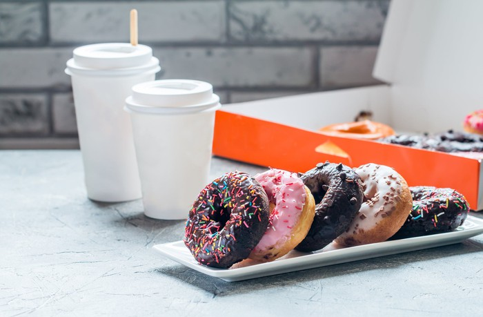 """A box of doughnuts with cups of """"to go"""" coffee."""