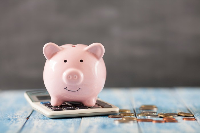 Piggy bank with calculator and change.