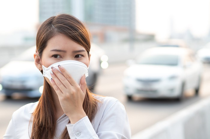 A young Asian woman, wearing a surgical face mask, stands next to a busy city street.