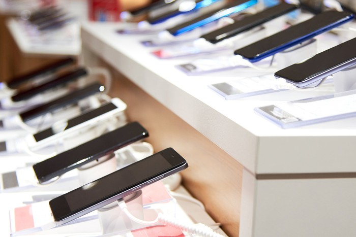 Photograph of smartphones on display in wireless service store.
