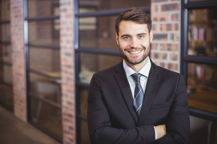 Smiling man in business suit with arms crossed