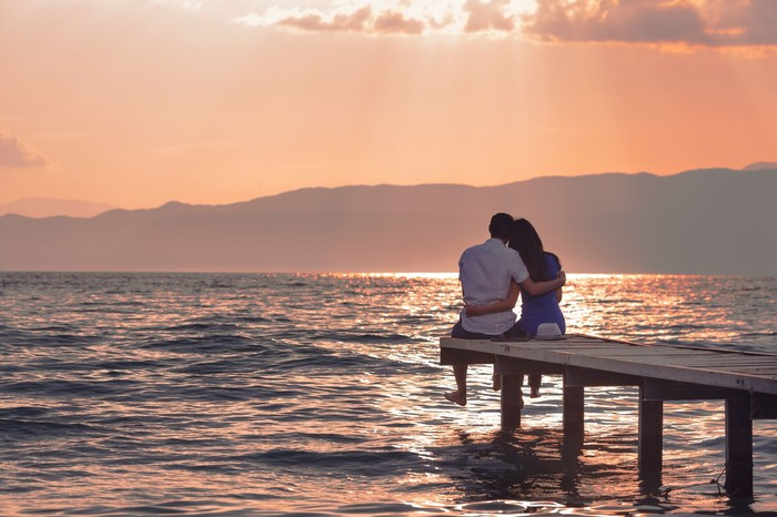 Couple sitting on a dock watching a sunset