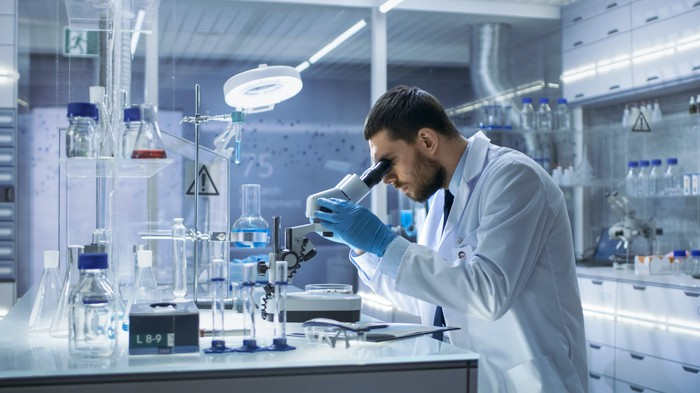 A scientist in a lab looking through a microscope.