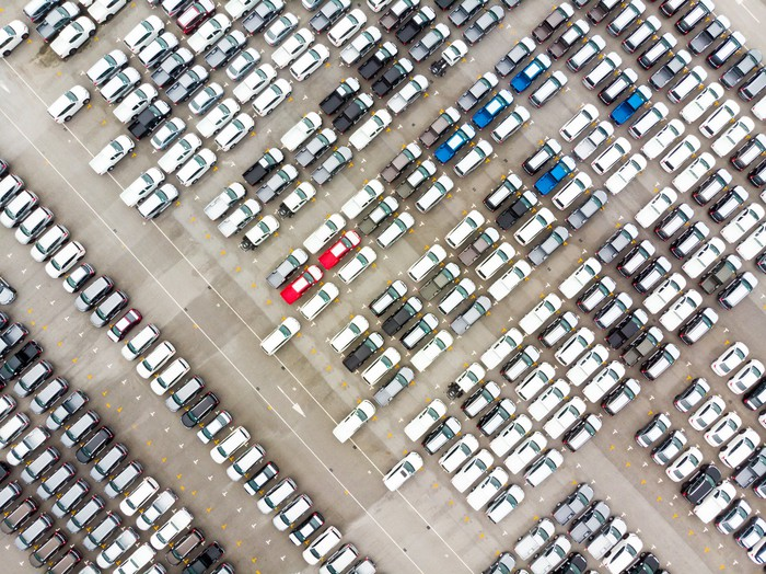 An overhead shot of hundreds of new cars waiting for shipment at a port lot.