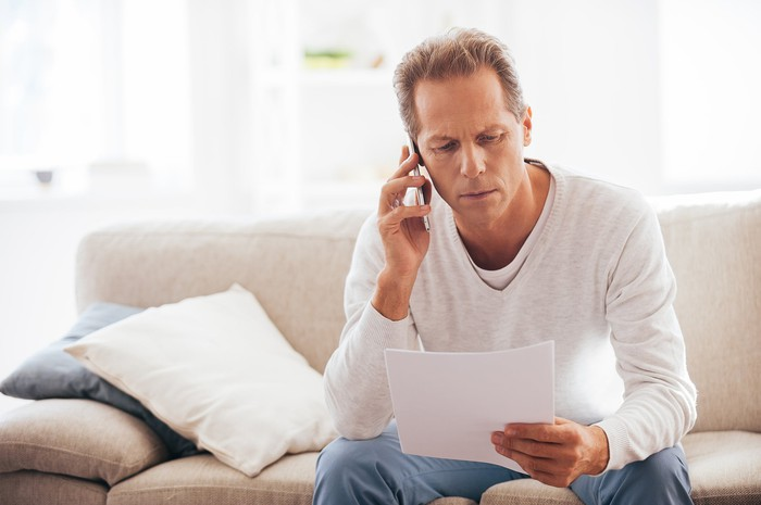 Older man reviewing paperwork while on the phone