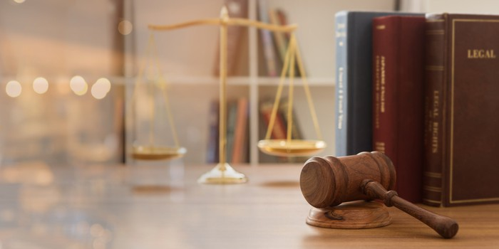 A gavel and hammer, law books, and a scale on a wooden table.
