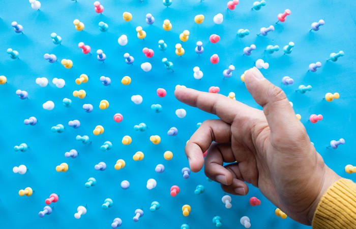 Finger pointing at pushpins on a blue field