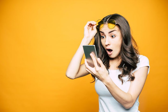 A woman checking her phone in surprise.