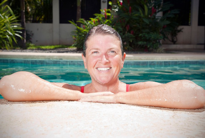 Smiling older woman resting arms on pool ledge