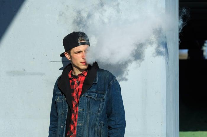 Young man exhaling vapor