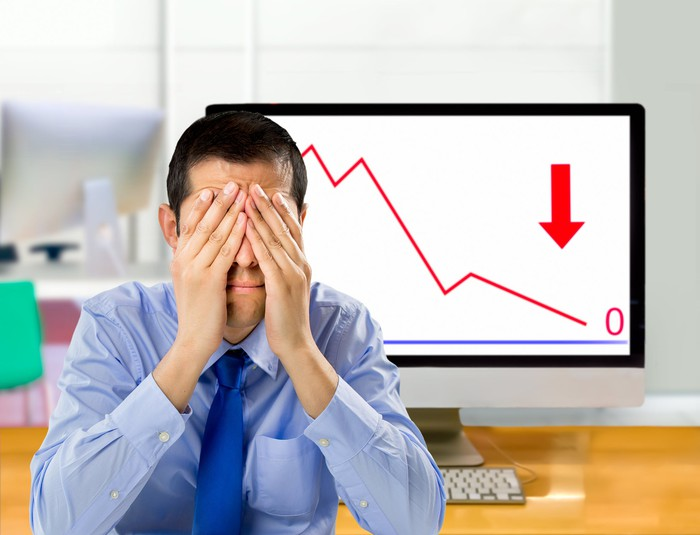 Man covering his face in front of screen showing downward graph