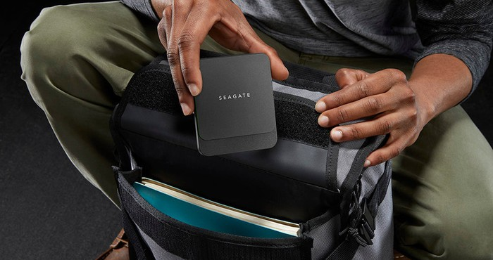 Traveler putting a Seagate hard drive into a backpack