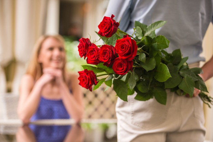 Person approaching seated woman holding roses behind their back.
