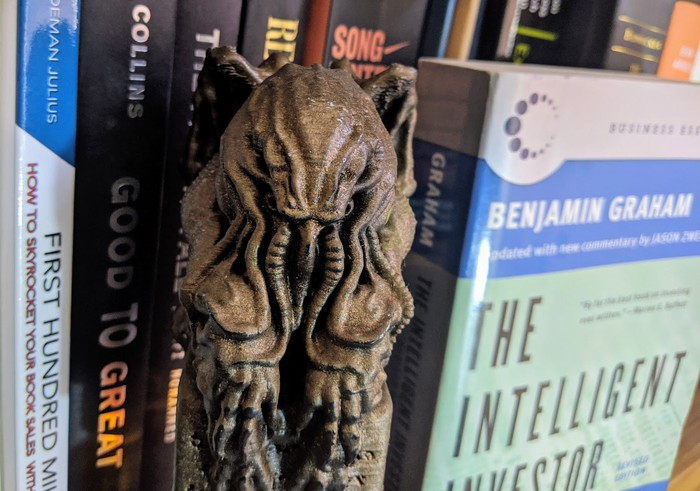 A 3D-printed Cthulhu statuette stands on a bookshelf between several great books about investing.