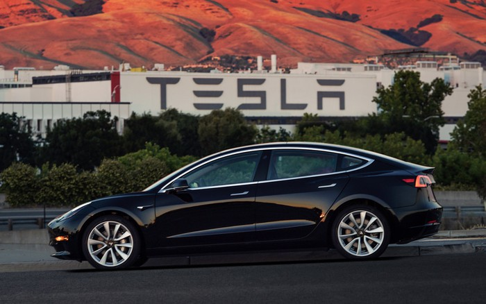 The first production Tesla Model 3 in black with Tesla factory in the background.