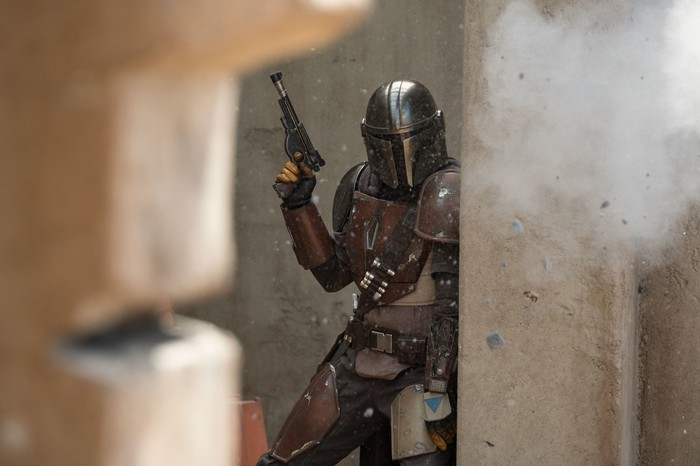 A man in an armor suit holding a gun while taking fire and hiding behind a concrete wall