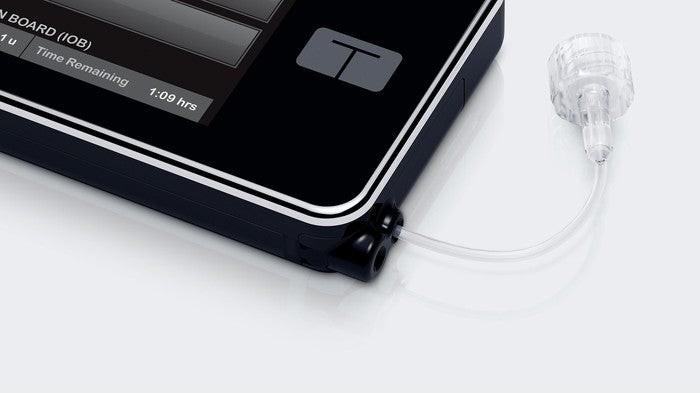 A t:slim X2 insulin pump lying on a flat surface.