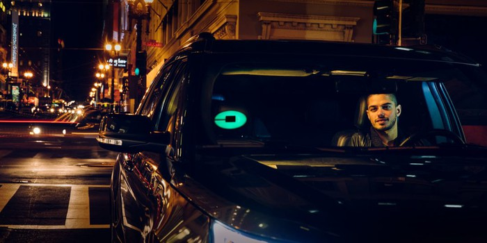 An Uber driver in his car at night with an illuminated Uber icon on the windshield.
