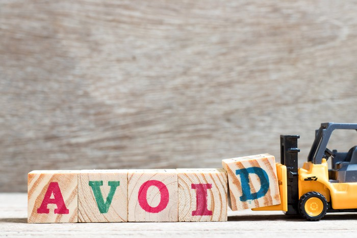 A toy forklift appearing to place wooden blocks in order that spell out the word avoid