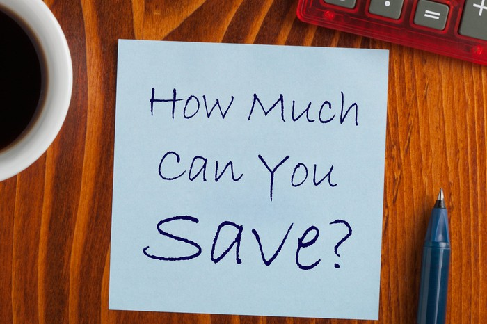 A paper is shown on a wooden surface and on it is written the question how much can you save?