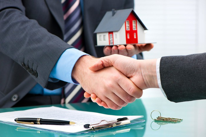 Two businessmen shaking hands, with a contract on the table and one holding a miniature house in their left hand.