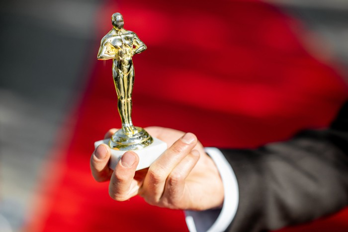 A hand holding up an unofficial copy of the famous Oscar statuette against the backdrop of a red carpet.