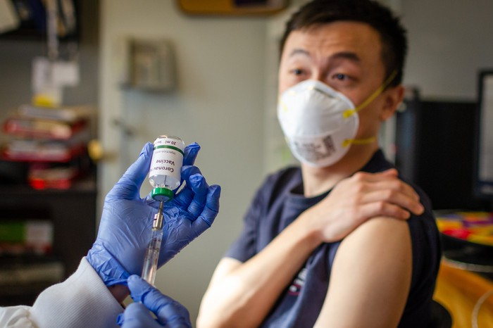 A person with a mask about to receive a vaccination.