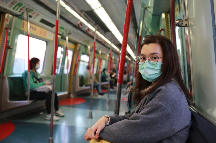 A woman wearing a surgical mask on a train
