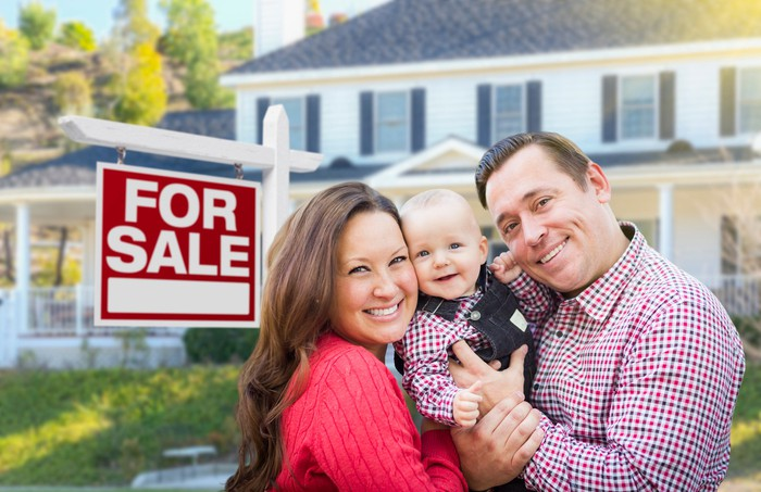 Smiling family in front of a home with a For Sale sign