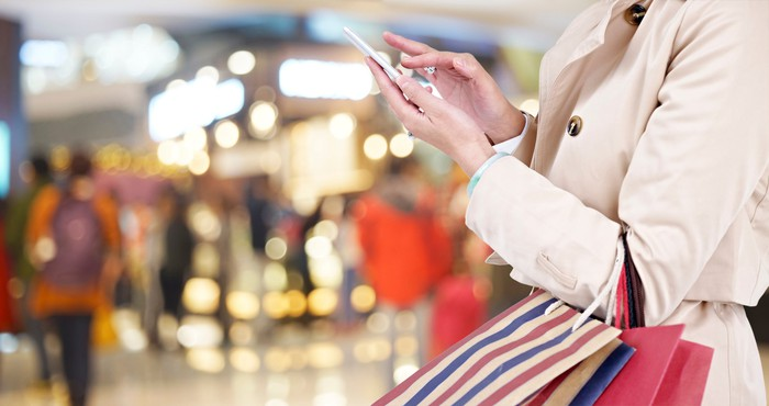A woman in a mall holds a phone and shopping bags.
